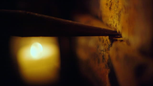 A man removes a brick from a wall illuminated by a lantern