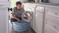MS TU Man removing laundry from washing machine into laundry basket, Phoenix, Arizona, USA