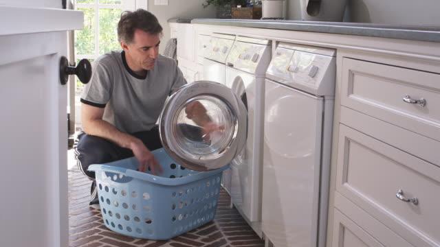 MS TU Man removing laundry from washing machine into laundry basket, Phoenix, Arizona, USA