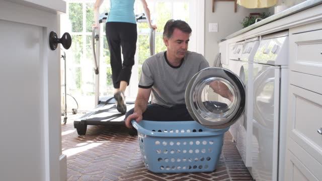 MS TU Man removing laundry from washing machine into laundry basket while woman exercising on treadmill in background, Phoenix, Arizona, USA