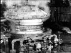 B/W 1925 man removing lid from steaming tire mold machine in Goodyear tire factory / industrial