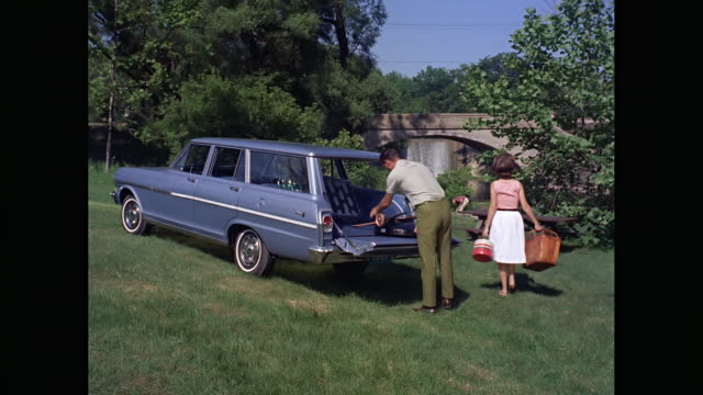 WS Man removing picnic basket and barbecue grill from 1963 Chevrolet station wagon car at picnic spot / United States