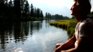 Man rests at edge of mountain creek, looks to mountains