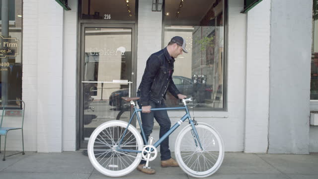 Man rides bicycle up to downtown storefront, props bike against building, and walks inside.