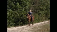 WS TS Man riding a horse on single track with trees in background / United States