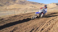A man riding a motocross motorcycle in the dirt. - Model Released - HD