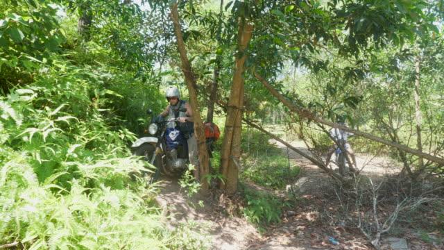 Mann reitet um Block im Trail auf seinem Motorrad