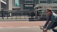 Uomo bicicletta di equitazione in ambiente urbano