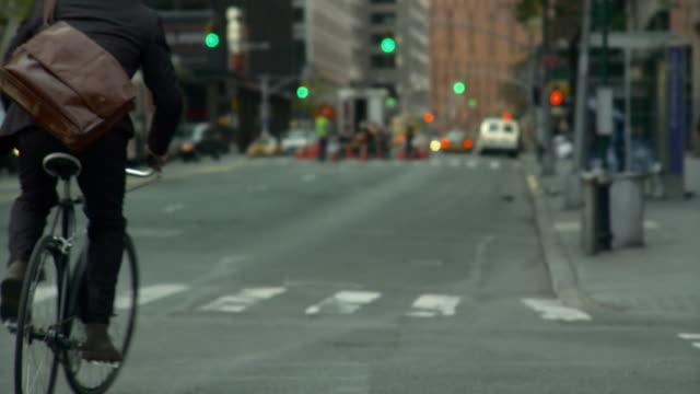 CU TU WS Man riding bike on busy street / New York City, New York, USA