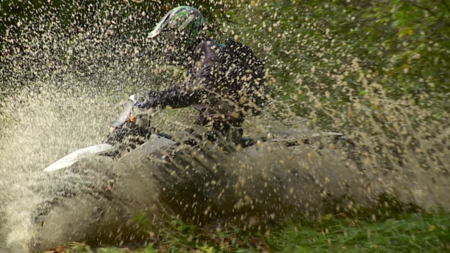 SLO MO WS PAN Man riding dirt bike through puddle in forest / Stowe, Vermont, USA