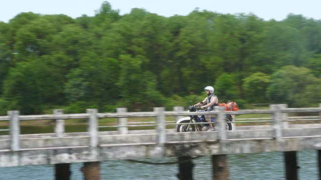 Mann auf seinem Motorrad über eine Brücke über dem Wasser