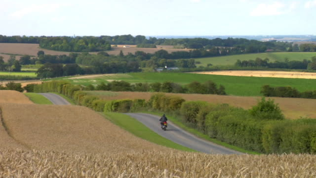 WS Man riding motorbike on country road / London, UK