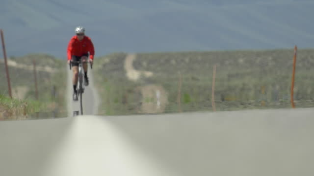 A man road biking on a scenic desert road. - Slow Motion
