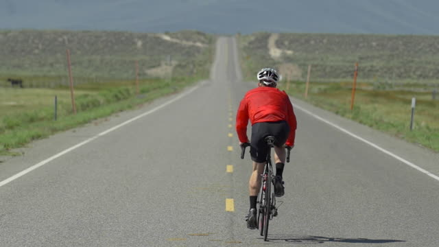 A man road biking on a scenic road. - Slow Motion