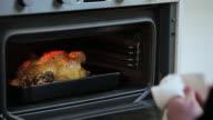 Man roasting chicken in oven