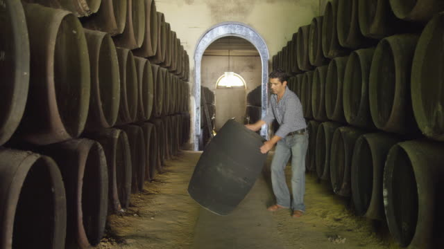 R/F man rolling barrel to camera through corridor between long rows of wooden casks; sets barrel down and walks out of frame