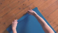 Man rolling out Yoga mat at Home