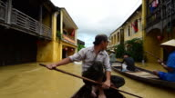 man Rowing boat along flooded streets, Hoi An, Vietnam