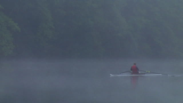 WS PAN RV Man rowing in single scull on the Connecticut River in fog at dawn/ Hanover, New Hampshire, USA