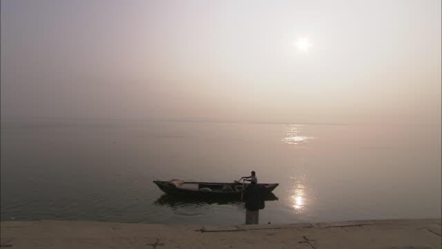 A man rows a canoe across a golden river where another man wades, waist deep.