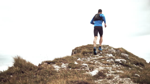 SLO MO Man running across a mountain ridge on a rocky trail in the grass