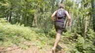 TS Man running across forest undergrowth