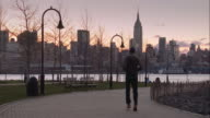 Man Running Along a Hoboken Park Path Overlooking Midtown Manhattan and the Hudson River
