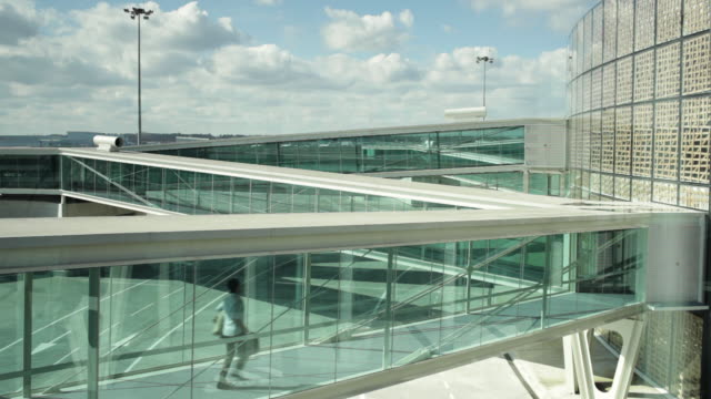 WS Man running along glass walkway towards airport building / Toulouse, Haute-Garonne, France