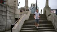 Man running around the city going down some stairs