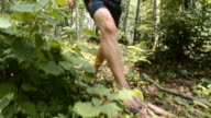 Man running barefoot across forest undergrowth