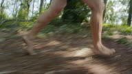TS TD Man running barefoot in the forest
