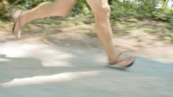TS Man running barefoot through the forest on a sunny day