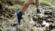 SLO MO Man running in an almost dried creek bed in sunshine