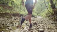SLO MO Man running in dried up creek in sunshine