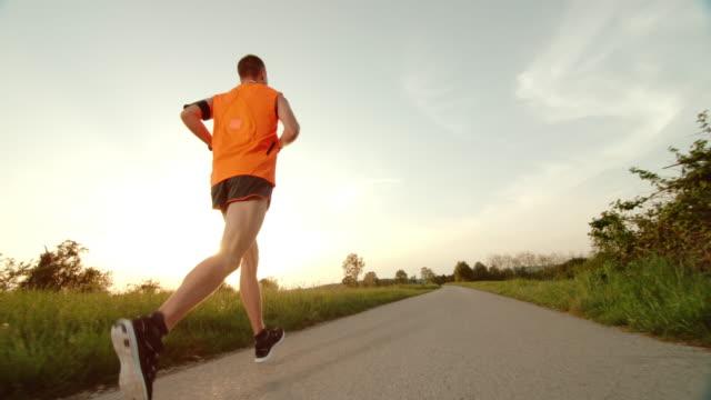 SLO MO TS uomo che corre al tramonto