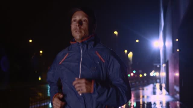 SLO MOTION uomo che corre in città di notte