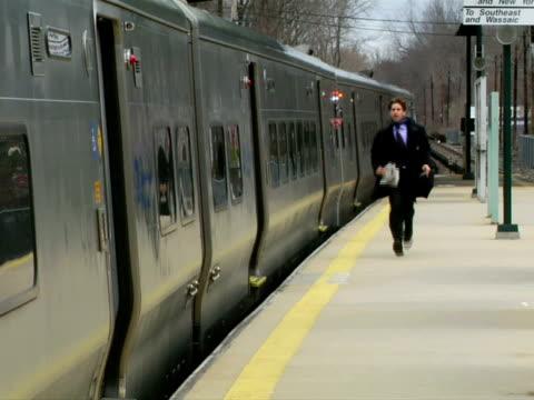 MS, Man running on railroad station platform along moving train, Chappaqua, New York State, USA
