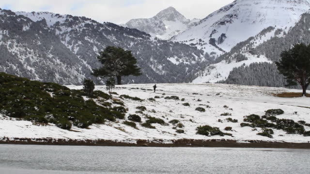 Man running on the shore of a lake in a snowy landscape amidst spectacular mountains