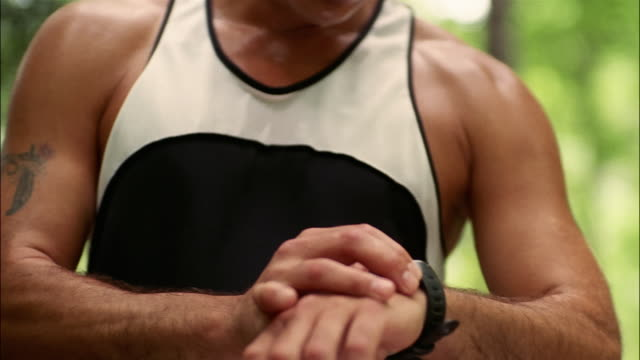 Man running on trail through woods / stopping and taking breath / checking watch / hunching over / resetting watch / wiping sweat off brow / Georgia