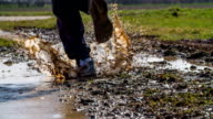 SLOW MOTION : Man running through muddy puddle