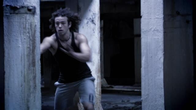 A man runs through a warehouse and jumps over a pole