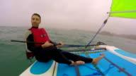 Man Sailing a catamaran On The Ocean.