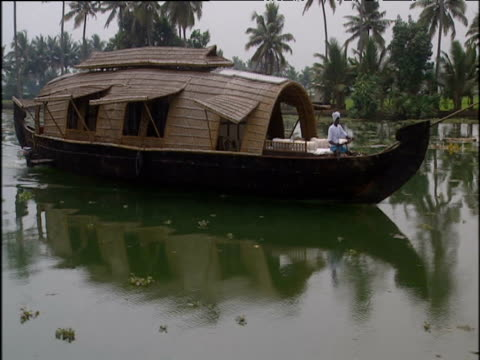 Man sailing houseboat to right along green colored river trees and houses in background; Kerala
