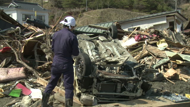 Man salvages tyres off his van which he just found in Kesennuma City, a traditional fishing town in N E Japan filmed on 1 April 2011, 3 weeks after a tsunami which was caused by magnitude 9 Tohoku earthquake off north east Japan / AUDIO