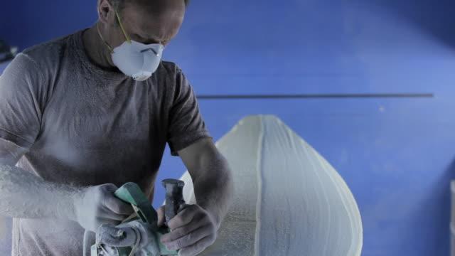 Man sanding new surfboard