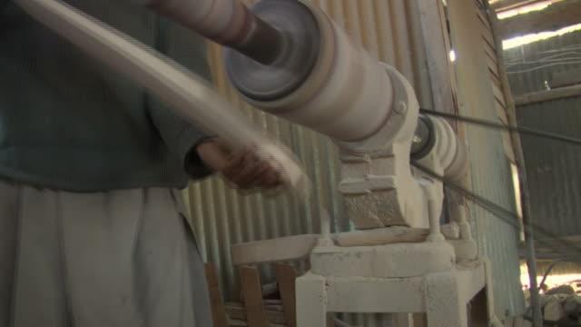 CU Man sanding wood for cricket bat in bat factory / Bijbehara, Jammu and Kashmir, India