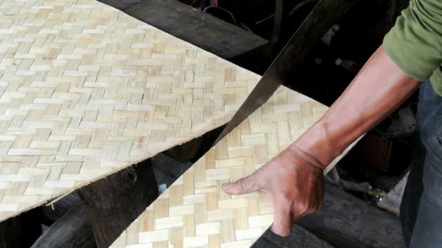 man sawing bamboo plywood sheet