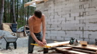 Man saws plank with a circular saw.