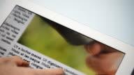 Mann Scrollen die Tageszeitung auf dem touch screen digital tablet