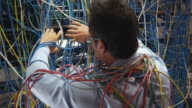 MS Man searching through server wall covered in cables, Sydney, Australia